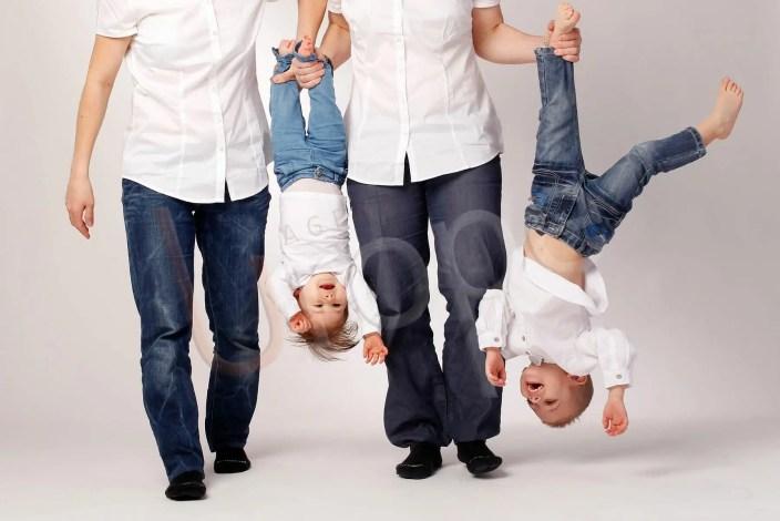 Photo de famille dont les parents tiennent les enfants par les pieds