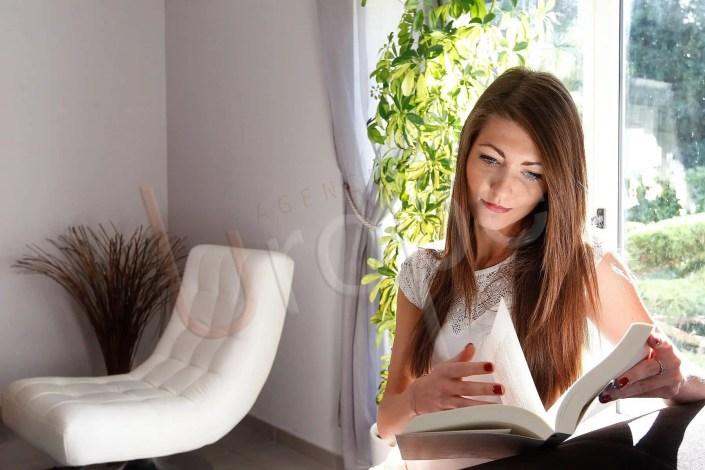 Photographie d'une femme qui lit un livre dans un hôtel