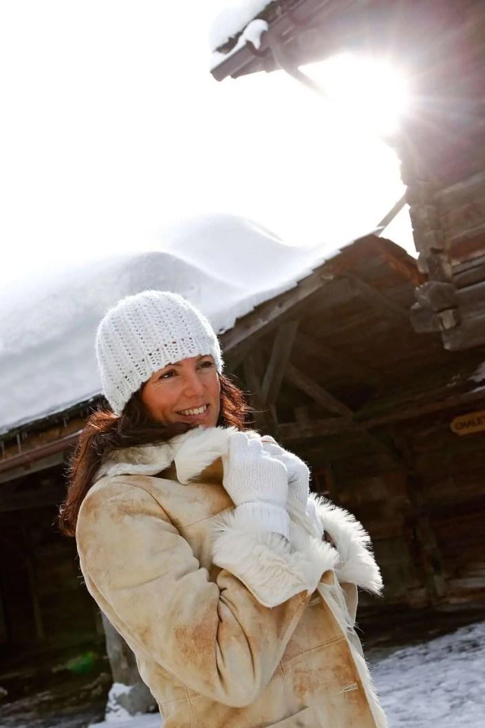 Portrait d'une femme sous la neige avec bonnet et gants