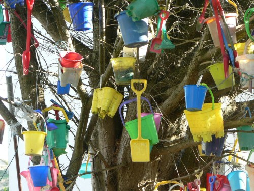 Image of bucket and spades in a tree