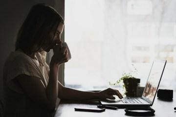 women at laptop side view window