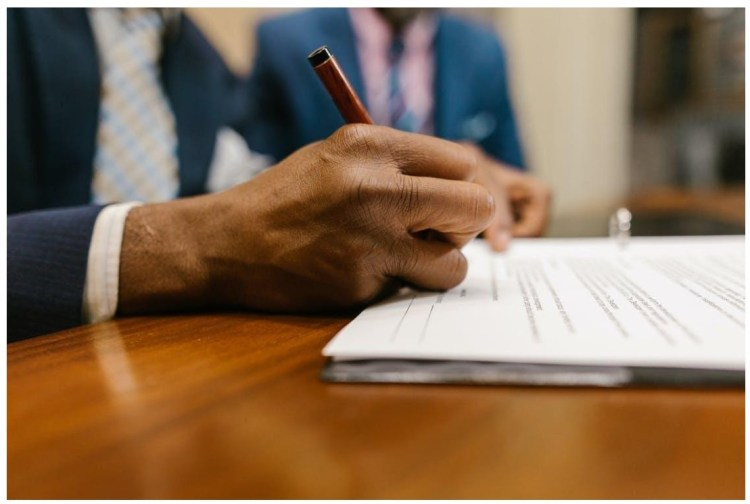 mans hand with pen signing legal contract