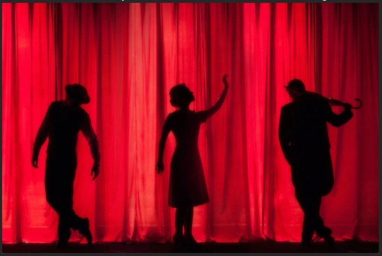 3 actors in shadow behind red curtin