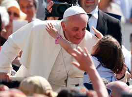 Pope Francis accepts a hug from a girl as he arrives to celebrate Mass in St. Peter's Square at the Vatican. (CNS photo/Paul Haring)