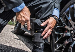 A man in a dark blue suit and light blue shirt squats beside a car in order to draw a small black revolver out of his ankle holster.