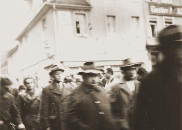Members of the SA and the Kraftfahr-Korps [motor corps] march Jewish men through the streets after their arrest during Kristallnacht. Erlangen, Germany. November 10, 1938.