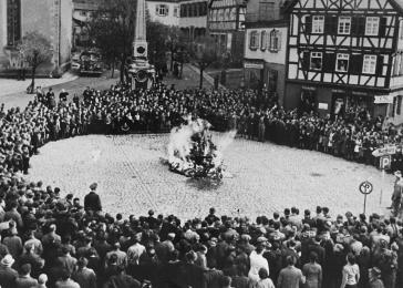 German civilians watch as the furnishings of the Mosbach synagogue are burned in the town square.