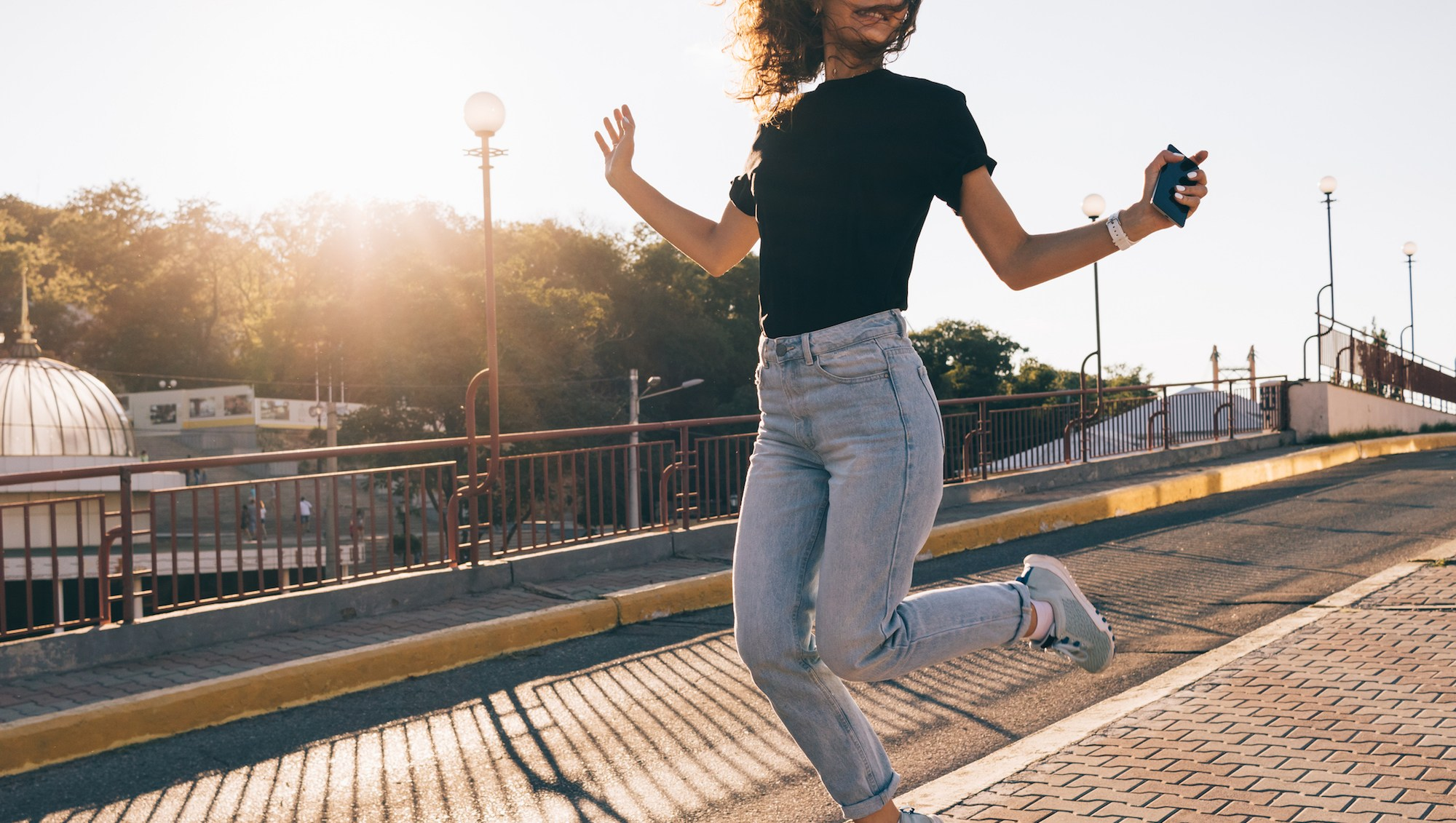 Happy girl with curly brown hair jumping in the city