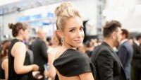 kristin cavallari looking over her shoulder smiling at the camera wearing a high bun, dangly earrings and a backless black gown