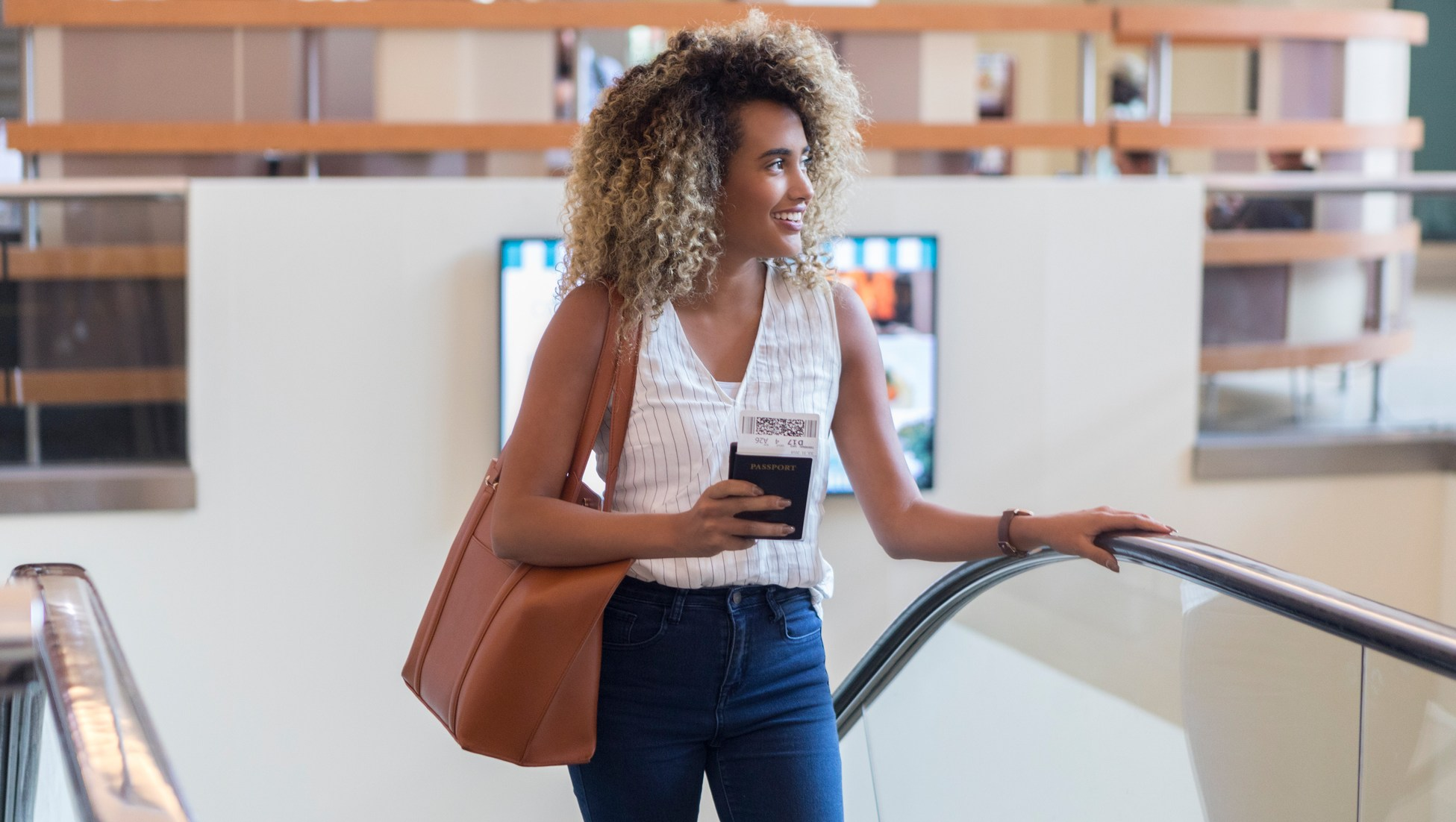 Young woman ascends escalator in airport terminal
