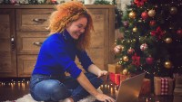Young beautiful girl with red curly hair ,enjoying at home in a cozy Christmas atmosphere while using lap top for online shopping.