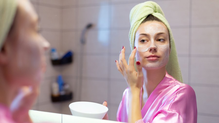 Beautiful young woman putting facial mask on her face in front of the mirror at home.