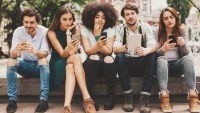 Group of mixed race people looking at mobile phones