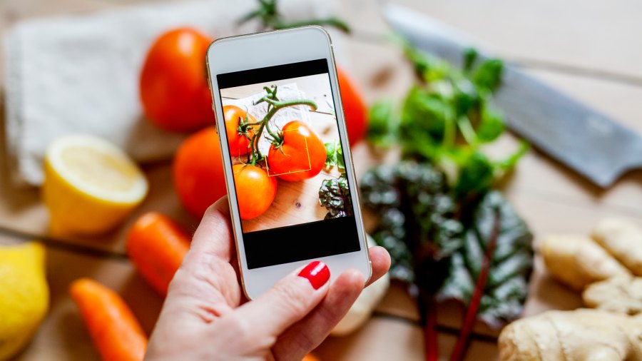 Woman photographing vegetables