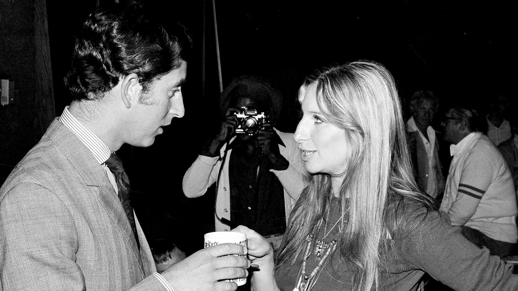 Barbra Streisand offers a cup of coffee to Prince Charles of Great Britain as they chat on a set at Warner Bros. studio in Los Angeles, CA, March. 19, 1974.