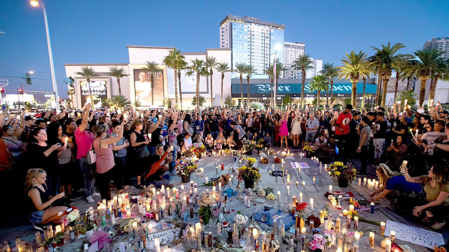 Mourners hold their candles in the air during a moment of silence during a vigil to mark one week since the mass shooting at the Route 91 Harvest country music festival, on the corner of Sahara Avenue and Las Vegas Boulevard at the north end of the Las Vegas Strip, on October 8, 2017 in Las Vegas, Nevada.