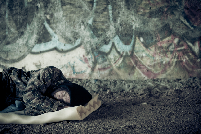 A homeless youth shelters under a bridge.