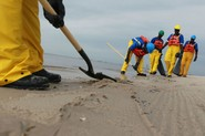 Workers clean the beach of debris as it is prepared for possible contamination from the massive oil spill in the Gulf of Mexico on May 3, 2010 in Pass Christian, Mississippi.