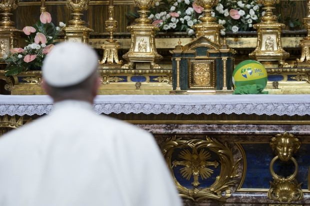 Pope Francis places a ball with the colors of the Brazilian flag at the altar of Saint Mary Major Basilica, in Rome.