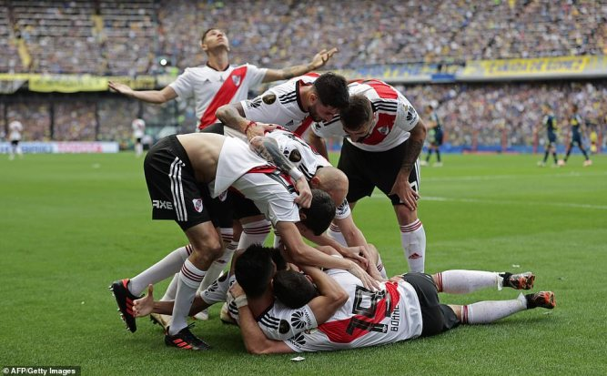 The River players bundled in the corner of the pitch after taking levelling through Carlos Izquierdoz's own goal