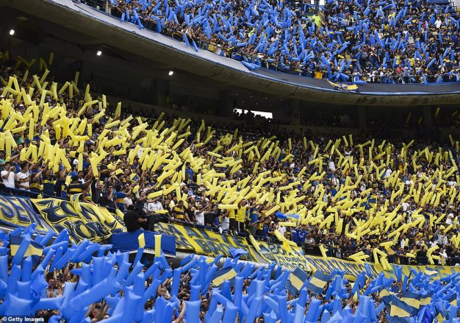 Boca Juniors' fans hold up yellow and blue inflatables to show their support ahead of the Sunday's first leg clash