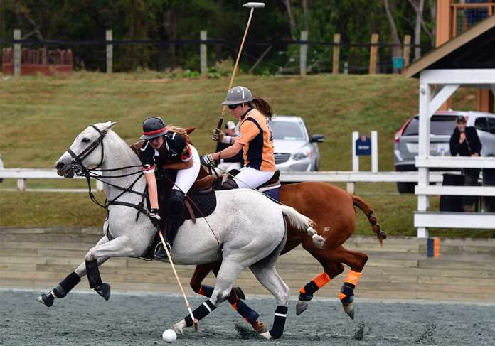 Sullivan Group'S Catie Stueck carries the ball on the nearside with Virginia Polo's Meghan Milligan defending. ©Kelly Wells