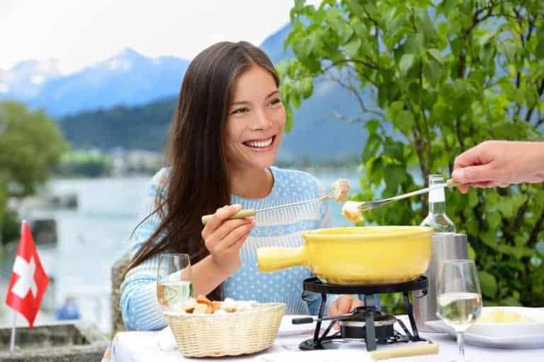 Donna che gusta la fonduta di formaggio