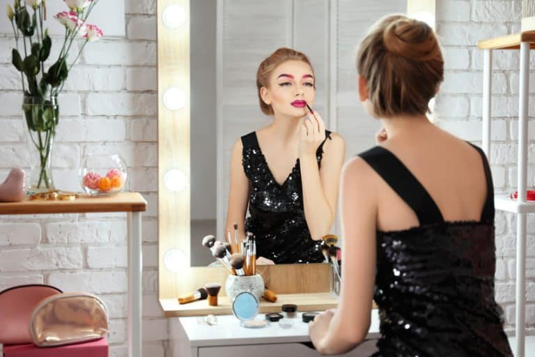 Donna che si trucca allo specchio