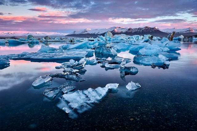 Sun sets over multiple small icebergs