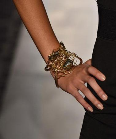 crna haljina i zlatne narukvice