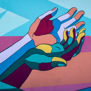 A painted mural of hands held out together in a cupped position