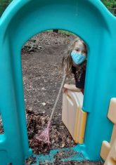 Small child raking leaves outdoors as seen through a green play doorway