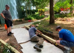 Three volunteers building a garden wall outside the church building