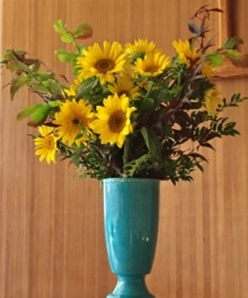Yellow sunflowers in a bright blue vase