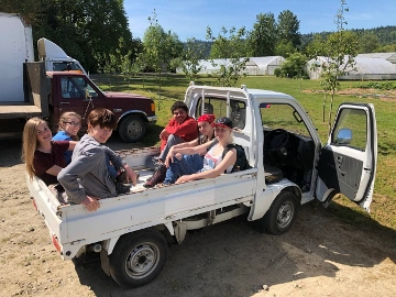 UUC youth sitting in the bed of a small white pickup truck