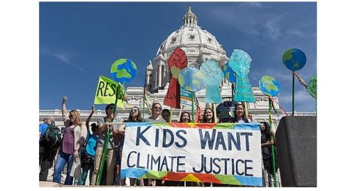 "Crowd of kids in front of government building with sign reading ""Kids Want Climate Justice"" - photo by Lorie Shaull"