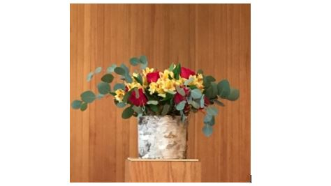 Flower arrangement with red and yellow flowers and eucalyptus leaves