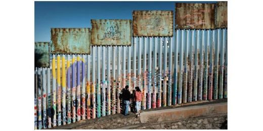 Woman and man standing next to border fence