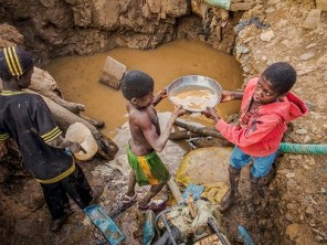 Two young boys use gold pans to carry water from the bottom of a 30-foot well at an artisianal mining site outside the town of Tiebele in central Burkina Faso.