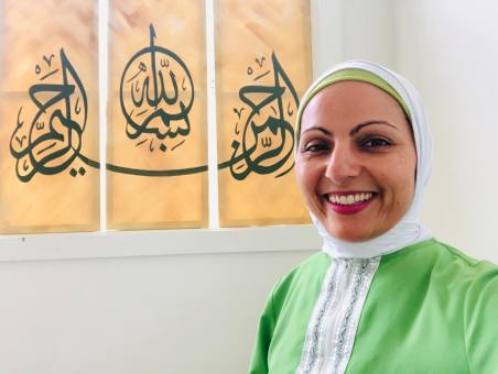 "Aneelah Afzali is the executive director of the American Muslim Empowerment Network, A program of the Muslim Association of Puget Sound. The writing behind her says ""In the name of God, the Most Gracious, the Most Merciful."""