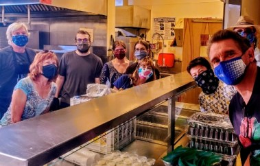 Seven smiling people, wearing masks, in an industrial kitchen
