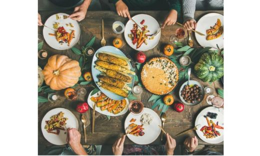 Dining table filled with plates of corn, squash, etc.; people eating - only see their hands and flatware