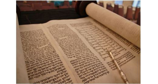 A torah scroll open to show three columns of Hebrew text and a silver yad (pointer)