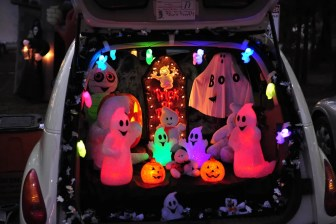"Back of a car open and showing decorations inside: string of lights and glowing ghosts and pumpkins and ""tombstone"" reading ""Trick or Treat"""