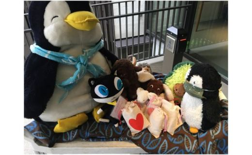 A collection of stuffed animals sitting on a blanket at the top of a UUC staircase