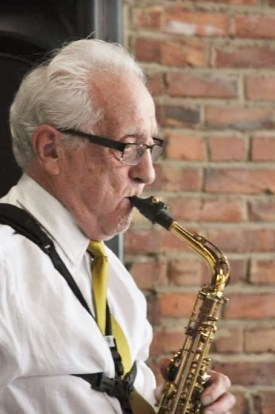 Pat Mann, dressed in a white shirt and tie, playing his sax
