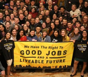"""A crowd of smiling young people holding a banner: """"We Have The Right To GOOD JOBS AND A LIVEABLE FUTURE"""""""