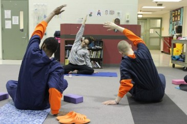 Yoga instructor and two students wearing prison garb
