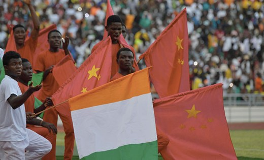 A group of performers hold Chinese and Ivorian flags during the inauguration ceremony of Ivory Coast's new 60,000-seat Olympic stadium, built with the help of China, in Ebimpe, outside Abidjan, on October 3, 2020 ahead of 2023 Africa Cup of Nations. (Photo by Issouf SANOGO / AFP) (Photo by ISSOUF SANOGO/AFP via Getty Images)