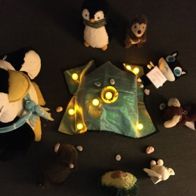 Stuffed animals sitting around a lighted chalice in a dim room